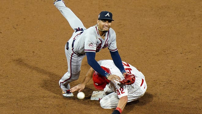 Atlanta Braves second baseman Johan Camargo, left, leaps over Philadelphia Phillies' J.T. Realmuto after forcing him out at second on a double play hit into by Jean Segura during the ninth inning of a baseball game, Sunday, Aug. 30, 2020, in Philadelphia.