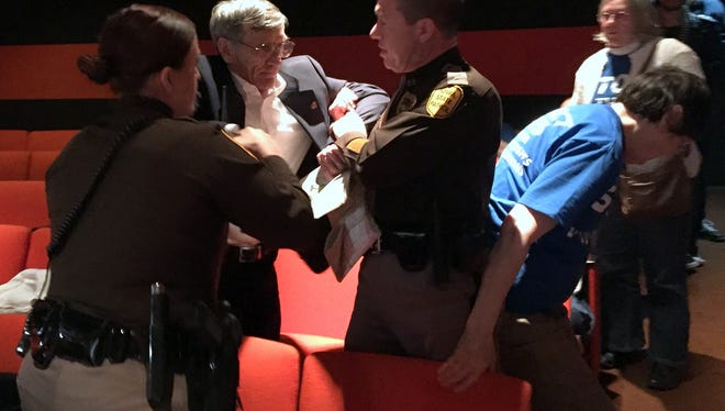 Trooopers escort Ronald Moyer of Des Moines from an Iowa DNR meeting Wednesday night in Des Moines after he allegedly became disruptive. The meeting was to discuss plans for a state environmental permit for a crude oil pipeline.