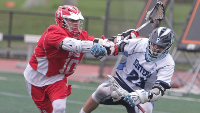Suffern's CJ Greco fights off a check from North Rockland's Kyle Michella during a Section 1 boys lacrosse game between Suffern and North Rockland at Suffern Middle School. Suffern won 14-13.