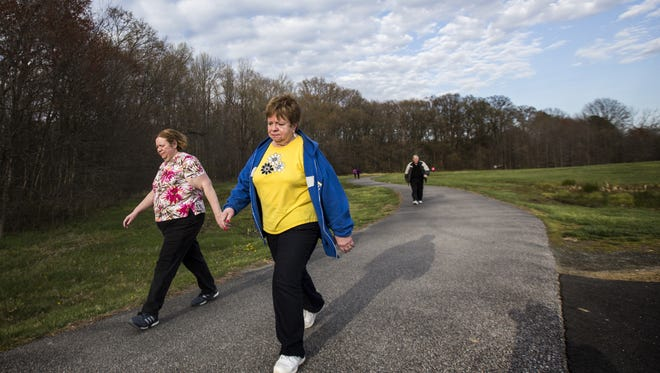 Barbara (center) and Larry Jester (right) walk with their daughter Debbie Goodchild (left) through Glasgow Park on Monday afternoon. The New Castle family is fighting diabetes by enrolling in a Type 2 prevention program run by the YMCA of Delaware.