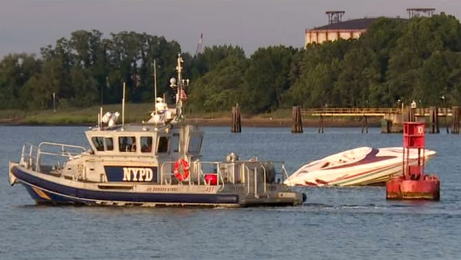 An NYPD marine unit passes by a boat that crashed into rocks off Woodbridge on Sunday, Aug. 13, leaving multiple people injured.