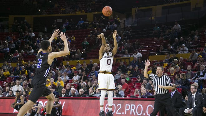 ASU's Tra Holder puts up a three point shot as Central Arkansas' Ethan Lee (left) defends during the first half at Wells Fargo Arena in Tempe on Thursday, December 22, 2016.
