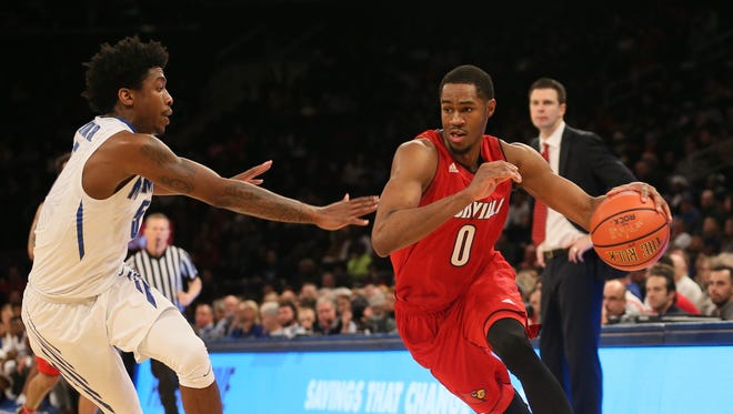 Louisville Cardinals forward V.J. King (0) moves the ball against Memphis Tigers guard Kareem Brewton Jr. (5) in the second half at Madison Square Garden in New York on Saturday, Dec. 16, 2017.