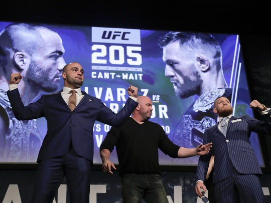UFC lightweight champion Eddie Alvarez (left) and featherweight champion Connor McGregor take the stage with UFC President Dana White during a news conference for UFC 205 on Tuesday. UFC 205 will take place on Nov. 12.