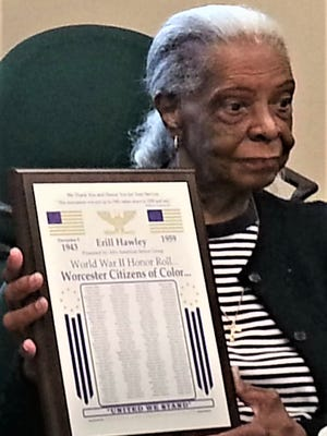 Jean Hawley holds a plaque commemorating the Colored Citizens of Worcester Honor Roll that recognizes Black Worcester residents who served in World War II, including Erill O. Hawley, Jean's late husband who was later appointed the first African American to join the Worcester Police Department.