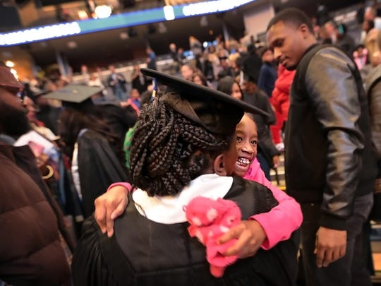 Annie Ivory, 52, gets a hug from her granddaughter Joi Simpson, 5, after getting her degree during the University of Memphis'  winter commencement at FedExForum.
