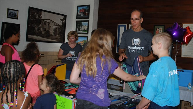 John Rinehardt stands by during Saturday's backpack giveaway at the Friendly House.