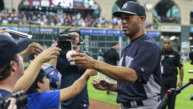 New York Yankees relief pitcher Mariano Rivera (42) signs autographs for fans before a game against the Houston Astros at Minute Maid Park.