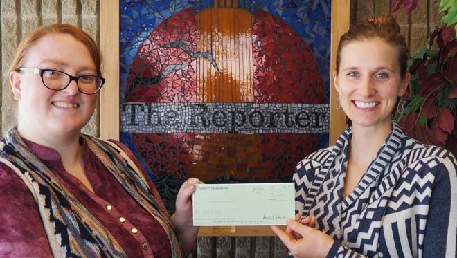 Jen Mattice, literacy director of Fond du Lac Adult Literacy Services, receives a check from Taima Kern of Wisconsin Media, part of the USA TODAY NETWORK.