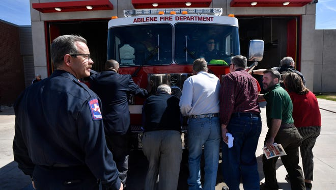 Abilene Fire Department Chief Larry Bell, left, walks behind a group of former and current Abilene City Council members and residents as they ceremoniously push a fire engine into the new Station 7 Friday. During the station's dedication, Bell announced he will retire May 31.
