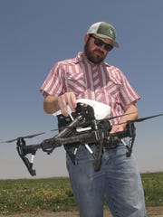 In this photo taken July 25, 2016, Danny Royer, vice president of technology at Bowles Farming Co., prepares to pilot a drone over a tomato field near Los Banos, Calif. The farm hired Royer this year to oversee drones equipped with a state-of-the-art thermal camera. The drone can scan from a bird's-eye view for cool, soggy patches where a gopher may have chewed through the buried drip irrigation line and caused a leak of water, a precious resource in drought-stricken California. On the farm's 2,400-acre tomato crop alone, this year drones could detect enough leaks to save water needed to sustain more than 550 families of four for a year. (AP Photo/Scott Smith)