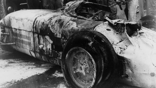 Workers at the track turn Bill Vukovich's car back onto its wheels after it flipped and burned during the 1955 Indianapolis 500.  Vukovich was killed.