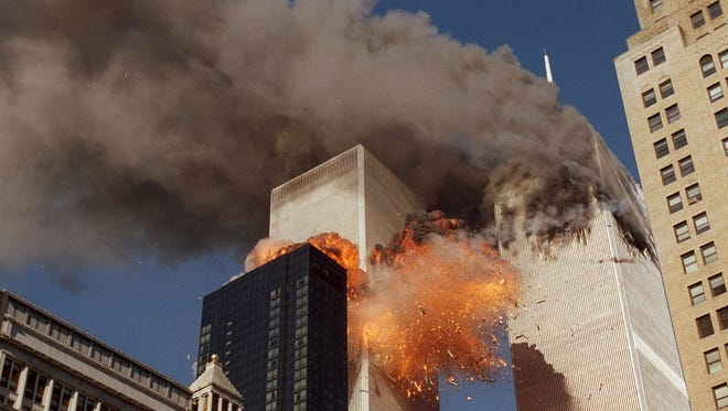 Smoke billows from one of the towers of the World Trade Center and flames and debris explode from the second tower.