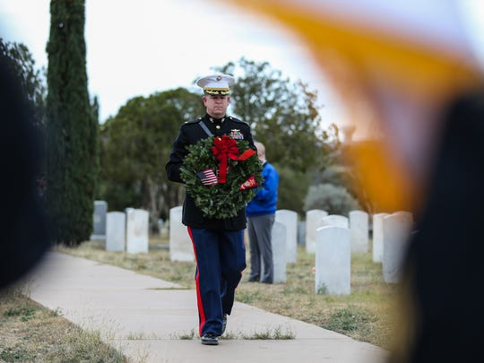 Marine Major Andrew Armstrong carries a wreath during the Wreaths Across America ceremony Saturday, Dec. 16, 2017, at Belvedere Memorial Park Cemetery.