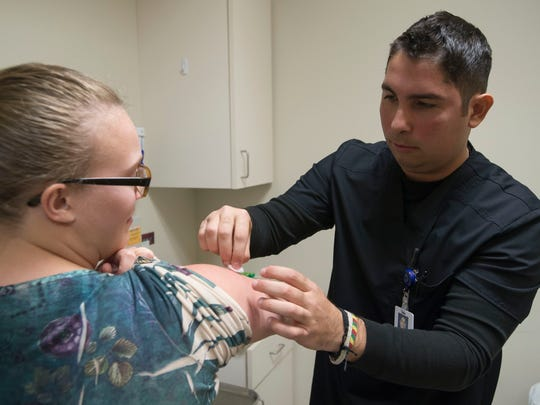 Medical assistants Jose Caceres administers swabs patient Maddie Woods arm after administering a flu vaccination on Wednesday, March 14, 2018, at Miramont Family Medicine on West Drake Road in Fort Collins, Colo.