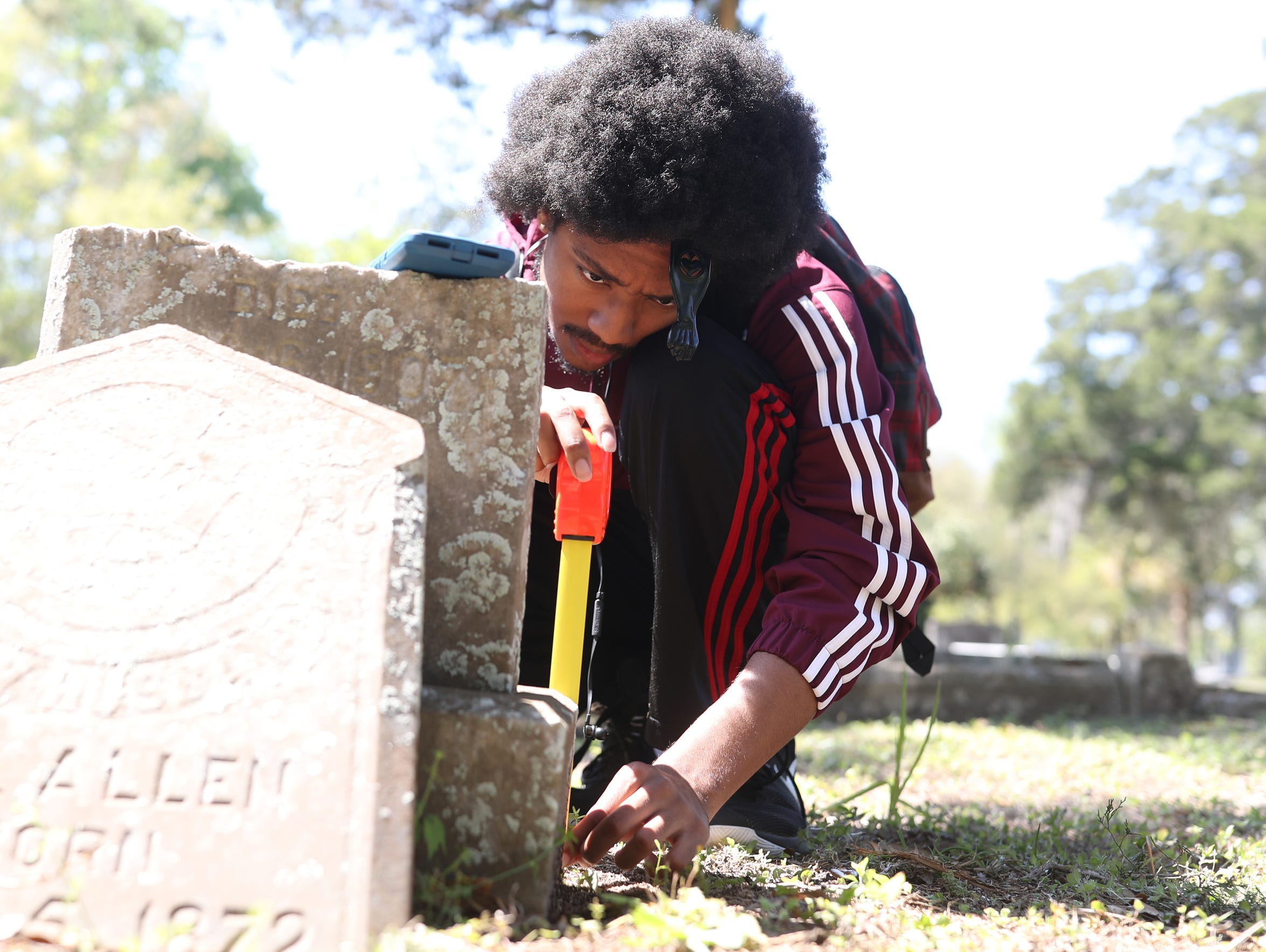 Terryon Larkins measures the height of a grave stone