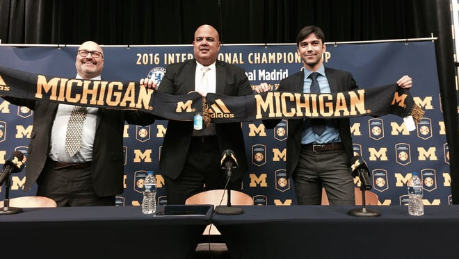 Michigan scarves are presented to Charlie Stillitano, left, chairman of Relevent Sports, and former Chelsea star and club ambassador Paulo Ferreira, right, at the Crisler Center on Thursday, March 24, 2016. U-M athletic cirector Warde Manuel is in the center.