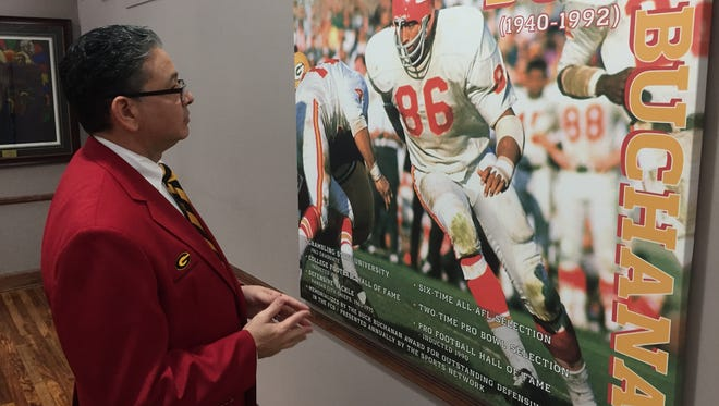 Grambling president Rick Gallot checks out a photo of Tigers legend Buck Buchanan, who will be one of four GSU players in the Pro Football Hall of Fame to be honored this weekend at the Super Bowl.