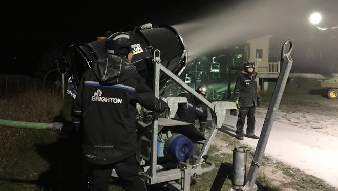 Mt. Brighton employees Michael Donner, Steve Hinson and William Ward position a snow making cannon at the top of a ski slope Sunday Nov. 19, 2017. Mt. Brighton's 2018 season starts Saturday.