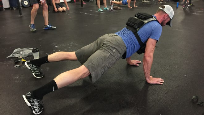 """U.S. Marine Corps veteran Sammy Pangle does push-ups as part of the Memorial Day """"Murph"""" workout at CrossFit Reaction in Greenville on Monday. A third-generation veteran, Payne said the workout """"is a big deal"""" for him."""