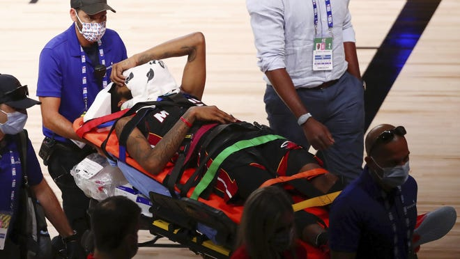 Miami Heat forward Derrick Jones Jr. (5) covers his face with a towel while he is taken off the court by medical personnel after colliding with Indiana Pacers center Goga Bitadze (not pictured) during the second half of an NBA basketball game Friday, Aug. 14, 2020, in Lake Buena Vista, Fla.