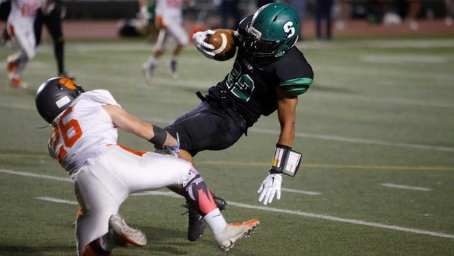 Farmington's Johnny Shuttleworth gets tripped up by Aztec's Hunter Riddick after a gain during Friday's game at Hutchison Stadium.