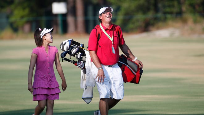 Lucy Li, 11, shares a laugh with her caddie as they walk up to the second green during a practice round for the U.S. Women's Open on Wednesday in Pinehurst, N.C.