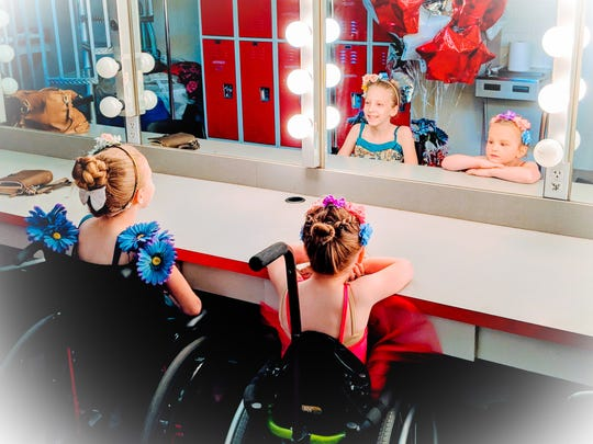 Maggie Braun, 9, (left) and Layla McCarthy, 5, view themselves in a mirror.