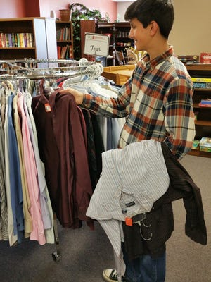 Brady Clauson, a freshman at Lincoln High School in Des Moines, volunteers at HCI Giving Tree thrift store in Urbandale. He helps prepare and place donated items to be sold in the store. Proceeds from store sales benefit the local non-profit HCI Hospice Care Services.
