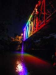 The Lone Wolf Bridge illuminates with the colors of the rainbow Monday, June 12, 2017, to honor Orlando's Pulse nightclub shooting victims on the first anniversary of the deadly attack.