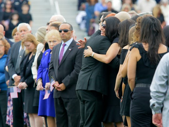Family members embrace during the funeral of Cpl. Daniel
