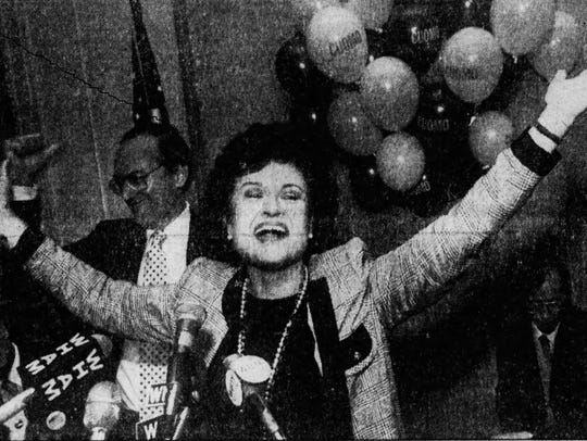 Louise Slaughter throws her arms in the air as supporters