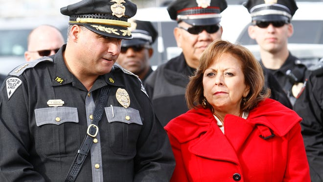 New Mexico State Police Chief Pete Kassetas stands next to New Mexico Gov. Susana Martinez on Thursday during a press conference along U.S. Highway 64 between Farmington and Bloomfield.