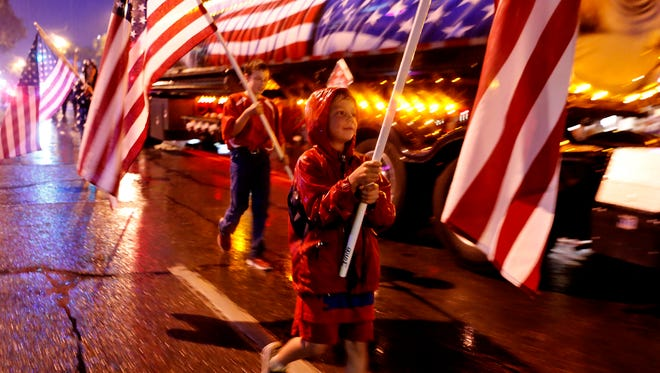 Participants march in the annual light parade march down Main Street in Farmington on July 4, 2015.