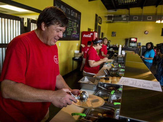 Owner Tony Robinson serves a customer during lunch at Papa T's Cafe.