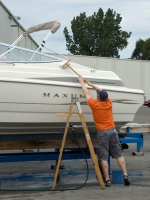 A man washes a boat as it is commissioned for another year on the water.