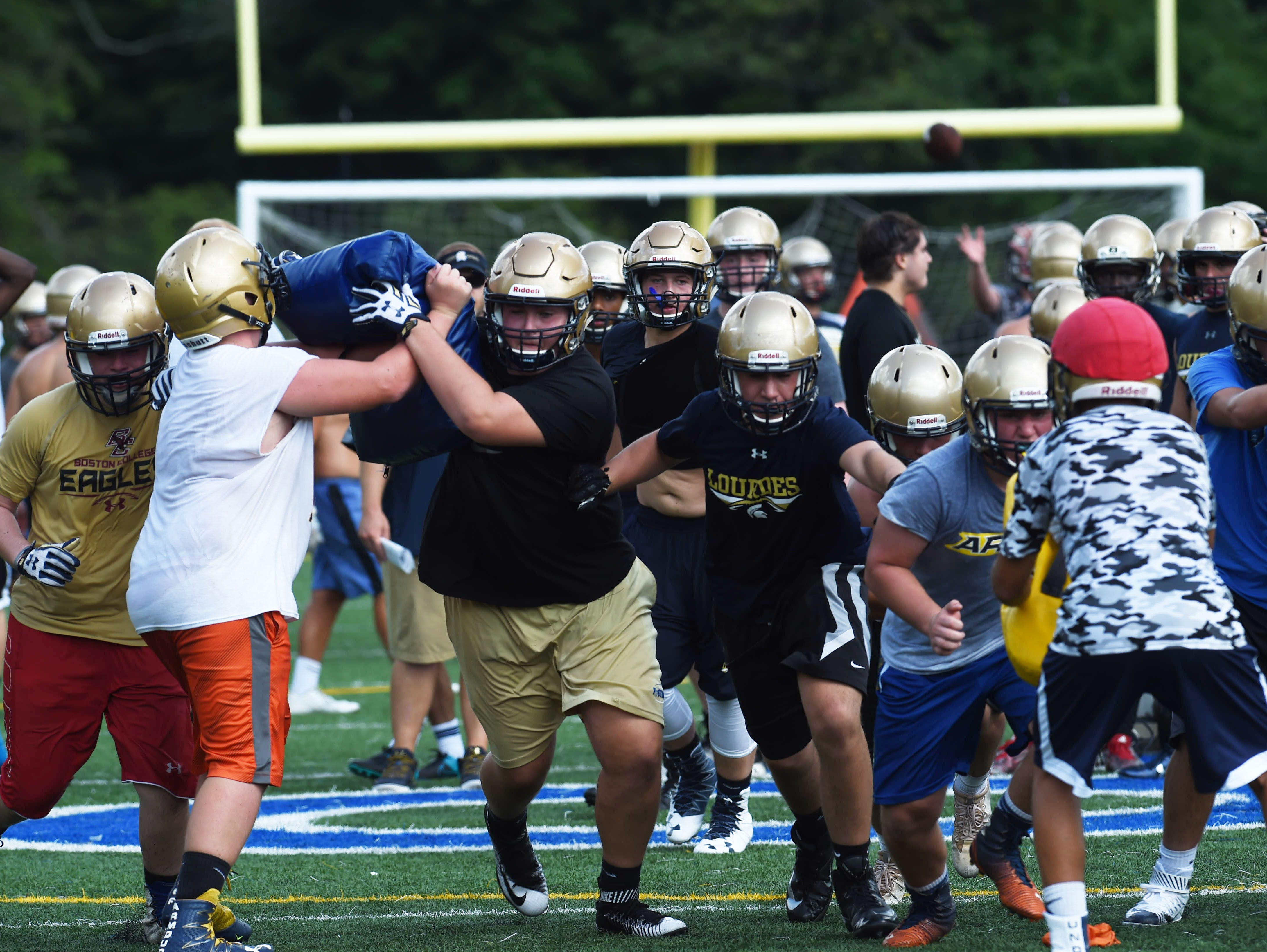 Junior Anthony D'Urso, center left, pushes past fellow junior Steven Garnot, left, during preseason football practice for Our Lady of Lourdes High School.