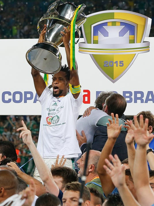 Palmeiras' Ze Roberto holds up the trophy as he celebrates with teammates after defeating Santos at the end of the Copa do Brasil final soccer match in Sao Paulo, Brazil, Thursday, Dec. 3, 2015. Palmeiras won in a penalty shootout after an aggregate 2-2 draw. (AP Photo/Andre Penner)
