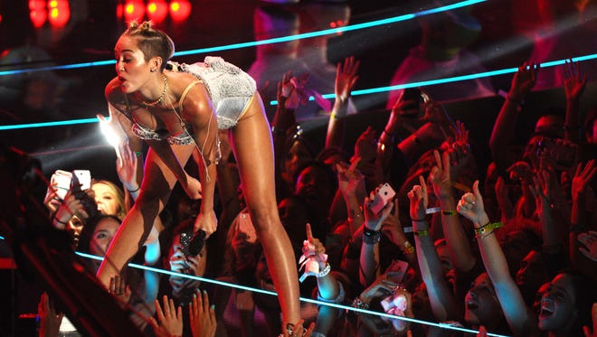 "File - In this Aug. 25, 2013 file photo, Miley Cyrus performs a move known as ""twerking"" at the MTV Video Music Awards at the Barclays Center in New York. Twerking may be older than you think. The provocative dance that gained global fame thanks to an attention-grabbing performance by Miley Cyrus has been admitted to the venerable Oxford English Dictionary _ and lexicographers say its origins go back almost 200 years. (AP Photo/Charles Sykes, Invision, File)"