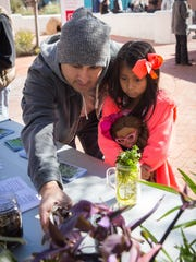 Omar Davila takes his 6-year-old daughter Arizai Davila on a family outing during a recent Houseplant Appreciation Day at the Branigan Cultural Center courtyard.
