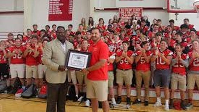 Patriots and Pro Football Hall of Fame linebacker Andre Tippett, now the team's executive director of Community Affairs, meets with the Barnstable Football players and coaching staff last fall to present a $1,000 donation on behalf of the Patriots Foundation, in honor of Coach Jatkola following the Red Raiders' 44-0 shutout win over Braintree.