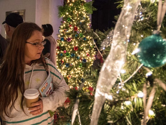 A woman looks at the Festival of Trees in the depot