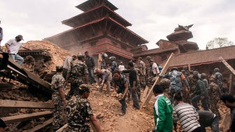 Rescue workers sift through the ruins of a building for possible survivors in Kathmandu, Nepal, Saturday.