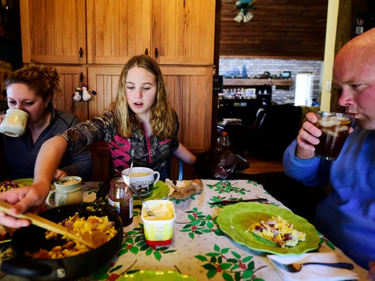 Taylor Howell, center, fills her plate as she eats breakfast with her stepmom Jess Howell, left, dad Brian Howell, right, and grandmother Cheryl Howell, not pictured. The family warmed up and swapped stories after a morning of hunting.