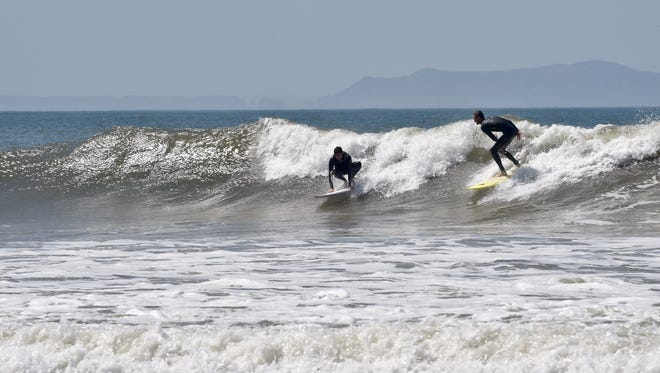 Surfers race for a wave at Ventura Beach during a past heat wave. Temperatures were expected to be in the 90s to 100s Thursday through Saturday, according to the National Weather Service in Oxnard.