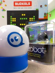 A Shpere (front), an Ozobot and Bloxels, all programable