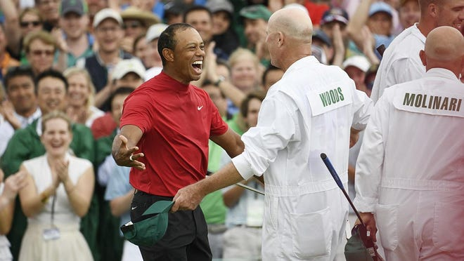 Tiger Woods goes to hug caddie Joe DeCava after winning  the Masters Tournament at Augusta National Golf Club, Sunday, April 14, 2019, in Augusta, Georgia.