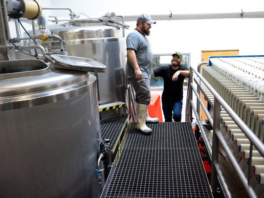 Coachella Valley Brewing Company brewmaster Chris Anderson (left) and brewer Ryan Markley (right) talk while brewing a batch of Monumentous beer on February 17, 2015 in Thousand Palms, Calif.
