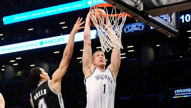 New Jersey Nets power forward Mason Plumlee dunks on Danny Green as the Nets defeat the Spurs, 103-89