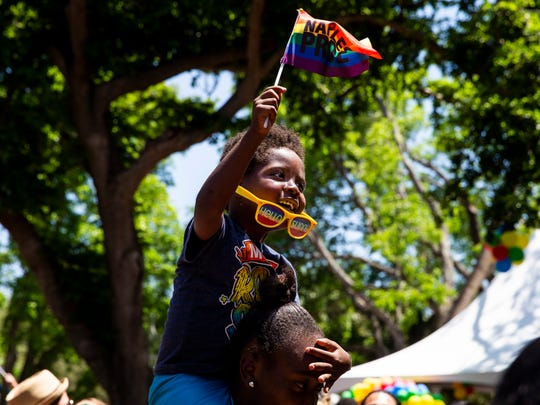Sharon Simmons, 4, waves his Naples Pride flag while